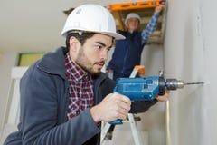 Стена цемента работника сверля Стоковая Фотография