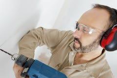 Стена человека сверля с перфоратором сверла стоковое изображение rf