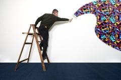 Стена человека крася белая с одичалыми цветами Стоковые Фотографии RF