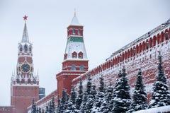 Стены Москвы Кремля красные после больших снежностей зимы, взгляда к красной площади с башней Senatskaya и Spasskaya возвышаются Стоковая Фотография
