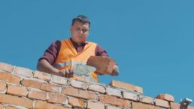 Стены строения каменщика в соответствии с планами строительства видеоматериал