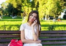 Стенд красивой девушки сидя, брюнет в розовом платье, образ жизни моды, говоря к телефону Стоковые Фотографии RF