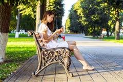 Стенд красивой девушки сидя, платье пинка брюнет, уклад жизни моды с вашим телефоном пишет сообщение на social Стоковые Изображения RF