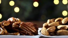 Стержени грецкого ореха, бразильская гайка и миндалины в шаре на деревенском старом деревянном столе с предпосылкой рождества Спо видеоматериал