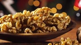 Стержени грецкого ореха в деревянную ложку на деревенском старом деревянном столе с предпосылкой рождества Сползите съемку сток-видео