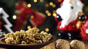 Стержени грецкого ореха в деревянную ложку на деревенском старом деревянном столе с предпосылкой рождества Сползите съемку видеоматериал