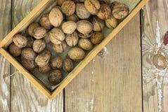 Стержени грецкого ореха и все грецкие орехи на деревенском старом деревянном столе плоский стиль положения Стоковое Фото