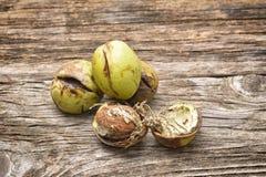 Стержени грецкого ореха и все грецкие орехи на деревенском старом деревянном столе Стоковые Изображения