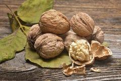 Стержени грецкого ореха и все грецкие орехи на деревенском старом деревянном столе Стоковые Изображения RF