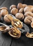 Стержени грецкого ореха и все грецкие орехи на деревянной предпосылке Стоковое Фото