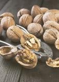 Стержени грецкого ореха и все грецкие орехи на деревянной предпосылке Стоковая Фотография