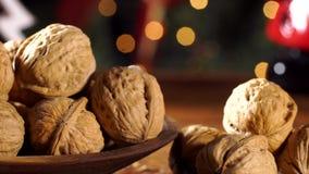 Стержени грецкого ореха на деревенском старом деревянном столе с предпосылкой рождества Сползите съемку видеоматериал