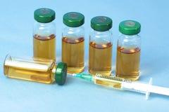 Стерильные медицинские пробирки с решением, ампулами, и шприцем на свете - голубой предпосылкой лекарства Стоковое фото RF