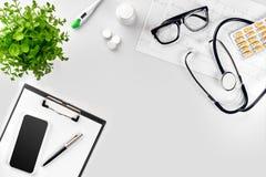 Стетоскоп в офисе докторов Взгляд сверху таблицы стола ` s доктора, чистого листа бумаги на доске сзажимом для бумаги с ручкой ск Стоковое Фото