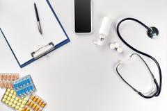 Стетоскоп в офисе докторов Взгляд сверху таблицы стола ` s доктора, чистого листа бумаги на доске сзажимом для бумаги с ручкой ск Стоковые Изображения
