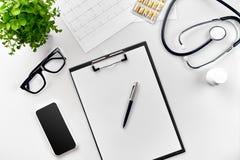Стетоскоп в офисе докторов Взгляд сверху таблицы стола ` s доктора, чистого листа бумаги на доске сзажимом для бумаги с ручкой ск стоковое изображение