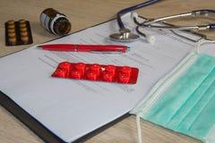 Стетоскоп в офисе докторов врачуйте таблицу стола ` s, чистый лист бумаги на доске сзажимом для бумаги с ручкой Стоковое Изображение