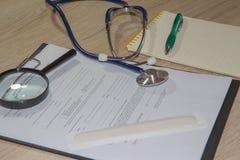 Стетоскоп в офисе докторов врачуйте таблицу стола ` s, чистый лист бумаги на доске сзажимом для бумаги с ручкой Стоковые Фотографии RF