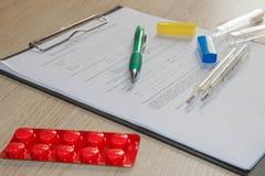 Стетоскоп в офисе докторов врачуйте таблицу стола ` s, чистый лист бумаги на доске сзажимом для бумаги с ручкой Стоковые Фото