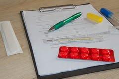 Стетоскоп в офисе докторов врачуйте таблицу стола ` s, чистый лист бумаги на доске сзажимом для бумаги с ручкой Стоковое Фото