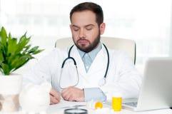 стетоскоп дег микстуры лож принципиальной схемы установленный Доктор сидя на столе в больнице Стоковая Фотография