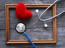 Стетоскоп для доктора Деревянная предпосылка и красное сердце, взгляд сверху Стоковая Фотография