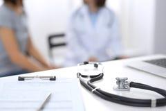 Стетоскоп, доска сзажимом для бумаги с медицинской формой лежа на приемной больницы с ноутбуком и занятый доктор и стоковые изображения rf