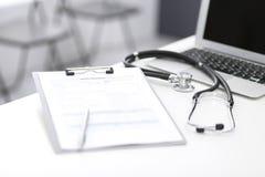 Стетоскоп, доска сзажимом для бумаги с медицинской формой лежа на приемной больницы с ноутбуком Медицинские инструменты на доктор стоковые изображения rf