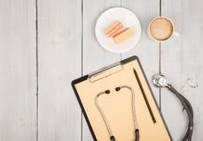 стетоскоп, доска сзажимом для бумаги, чашка кофе с waffles на белизне Стоковая Фотография RF