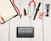 Стетоскоп, доска сзажимом для бумаги, smartphone с текстом & x22; ASTHMA& x22; , стекла, вахта и пилюльки стоковое изображение