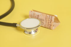 Стетоскоп и индеец примечания 10 рупий на желтом цвете Стоковая Фотография