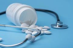 Стетоскоп и пилюльки медицины на голубой предпосылке Здоровье или заболевание стоковая фотография rf