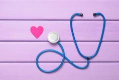 Стетоскоп и сердце на фиолетовом деревянном столе Оборудование кардиологии для диагностировать сердечно-сосудистые заболевания Вз стоковое фото