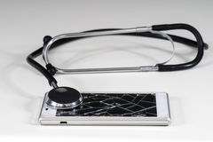 Стетоскоп и телефон на белой таблице Стоковое Изображение