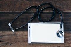 Стетоскоп и цифровая таблетка на предпосылке деревянного стола Стоковое фото RF