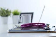 Стетоскоп, компьтер-книжка, папка на столе в больнице Стоковые Изображения