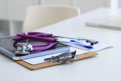 Стетоскоп, компьтер-книжка, папка на столе в больнице Стоковые Фото