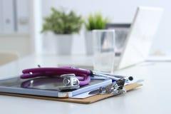 Стетоскоп, компьтер-книжка, папка на столе в больнице Стоковая Фотография