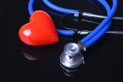 Стетоскоп, красное сердце и метр кровяного давления на черной предпосылке зеркала Селективный фокус стоковые фото