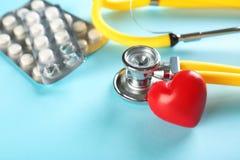 Стетоскоп, малое красное сердце и пилюльки на таблице Стоковая Фотография