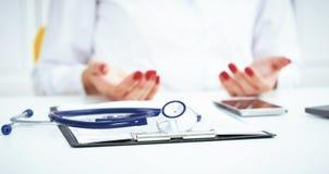 Стетоскоп, медицинская форма рецепта лежит на фоне доктора и пациента обсуждая экзамен здоровья стоковое фото rf
