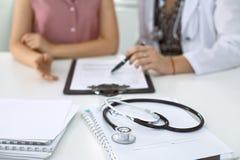 Стетоскоп, медицинская форма рецепта лежит на фоне доктора и пациента обсуждая экзамен здоровья Стоковое Изображение