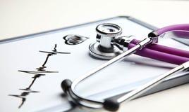 Стетоскоп при cardiogram лежа на столе в больнице Стоковые Изображения RF