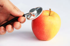стетоскоп руки яблока советуя с Стоковые Изображения