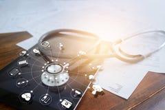 Стетоскоп с значком медицинским на backgrp таблетки и деревянного стола Стоковая Фотография RF