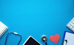 Стетоскоп с красной клавиатурой сердца и компьютера на голубой предпосылке МЕДИЦИНСКАЯ принципиальная схема стоковое изображение