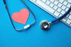 Стетоскоп с красной клавиатурой сердца и компьютера на голубой предпосылке МЕДИЦИНСКАЯ принципиальная схема стоковые фото