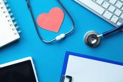 Стетоскоп с красной клавиатурой сердца и компьютера на голубой предпосылке МЕДИЦИНСКАЯ принципиальная схема стоковое изображение rf