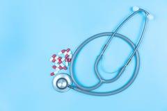 Стетоскоп с медициной капсулы на голубой предпосылке стоковое изображение rf