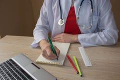 Стетоскоп с доской сзажимом для бумаги и компьтер-книжкой на столе Таблица деятельности ` s доктора медицины Стоковое Изображение RF